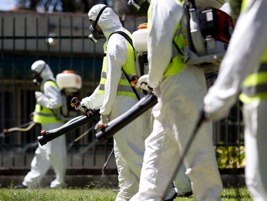 Nhân viên y tế phun thuốc diệt côn trùng. Ảnh minh họa: AP
